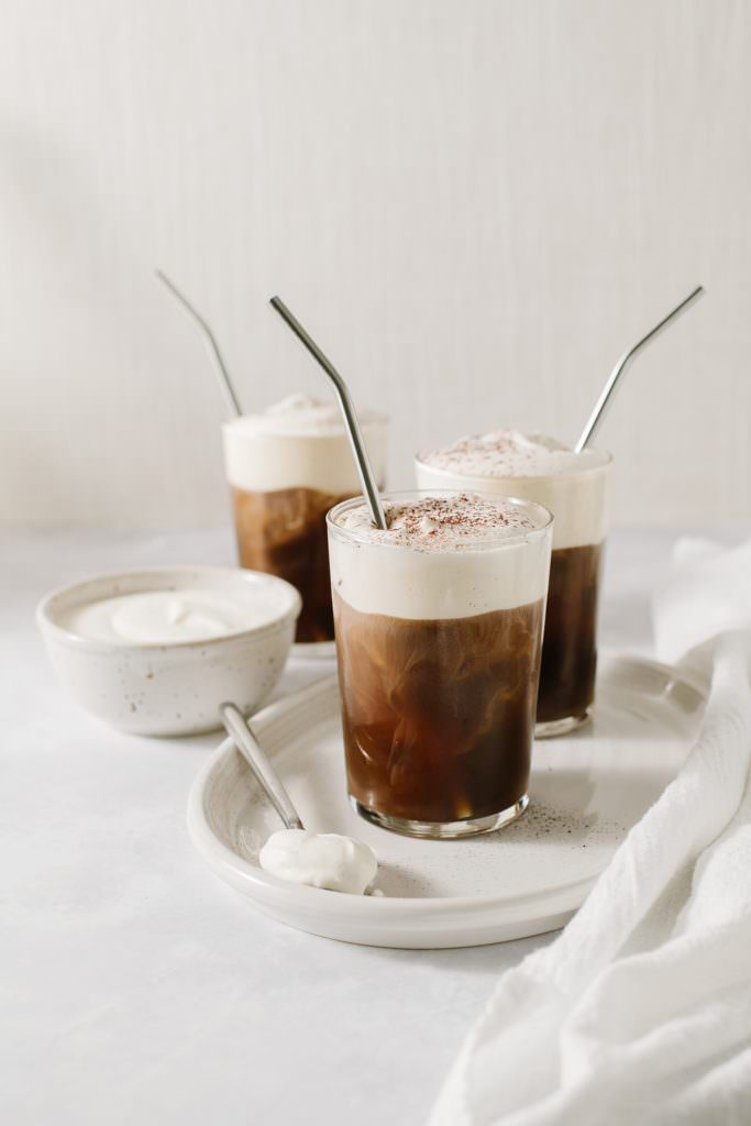 irish cream cold brew with metal straws on a tray with a bowl of cream