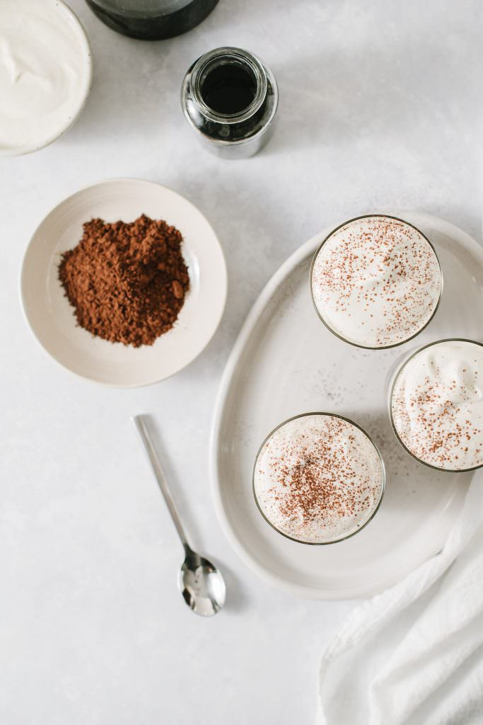 overhead shot of 3 glasses of irish cream cold brew on a platter with a spoon, a bowl of cocoa powder, and a bottle of homemade irish cream coffee syrup