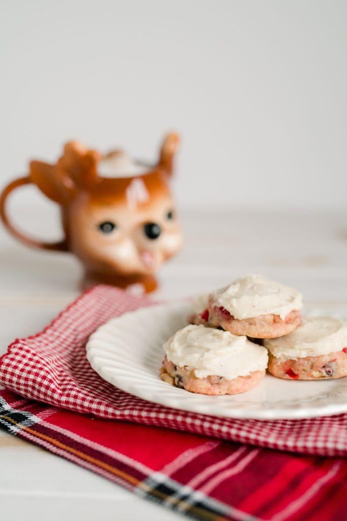 three christmas treasure cookies on a plate with a reindeer mug of cocoa