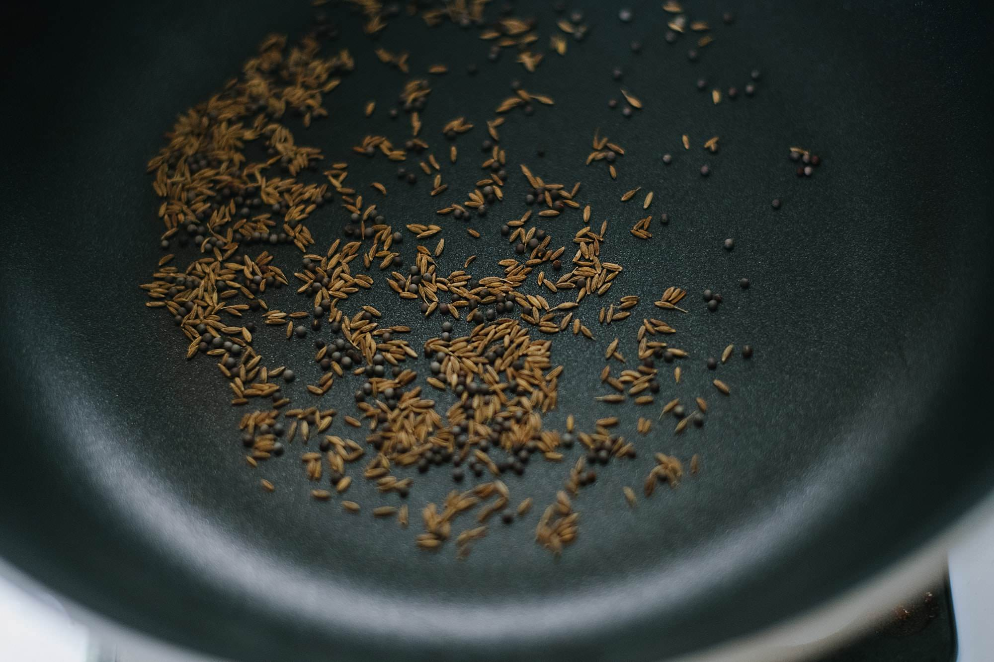 dry toasting cumin and mustard seeds in a pan