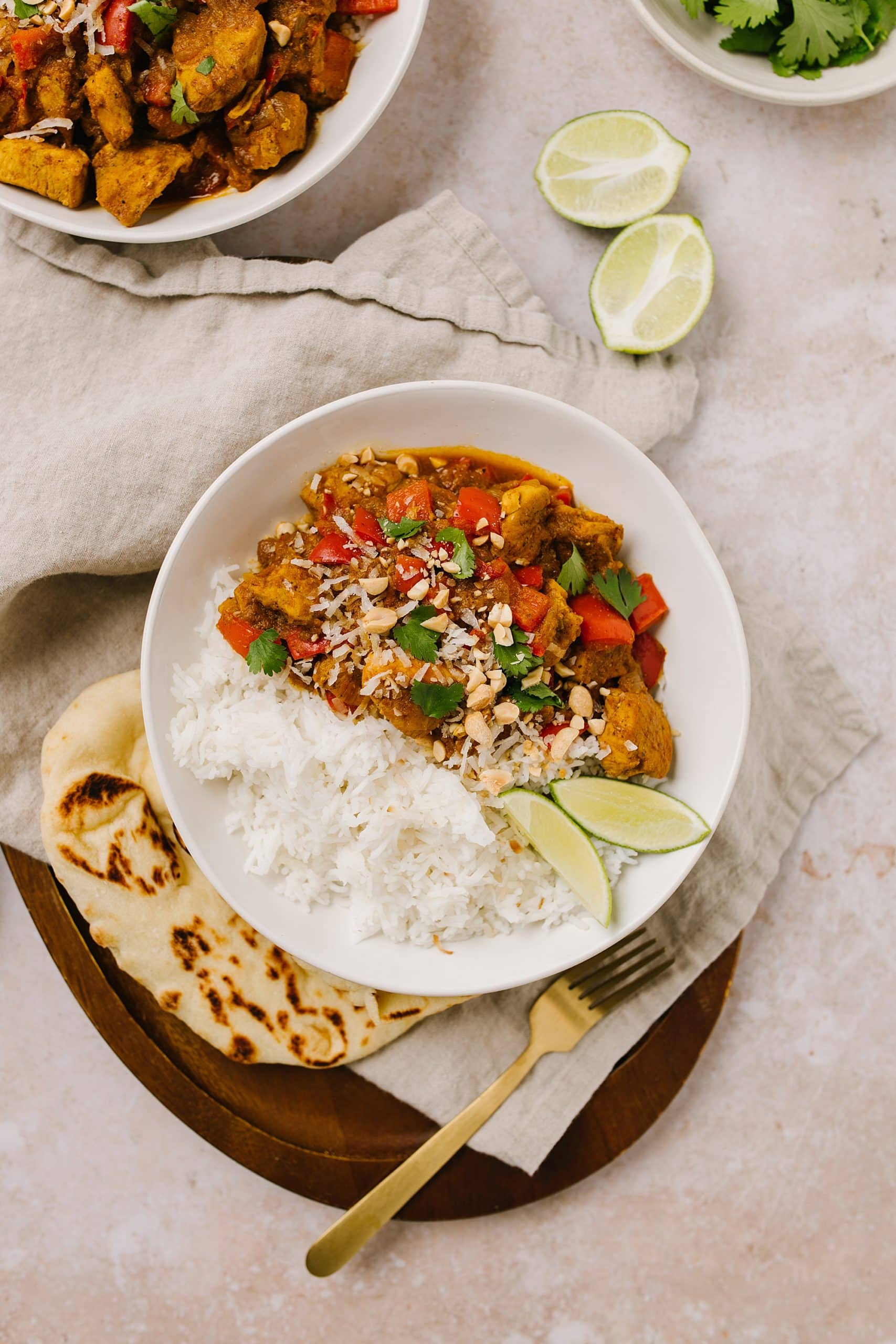 Easy Weeknight Chicken Curry Recipe in a bowl with rice with lime wedges and peanuts