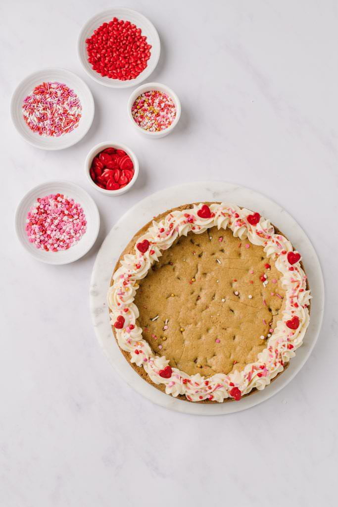 valentines cookie cake with five bowls of sprinkles
