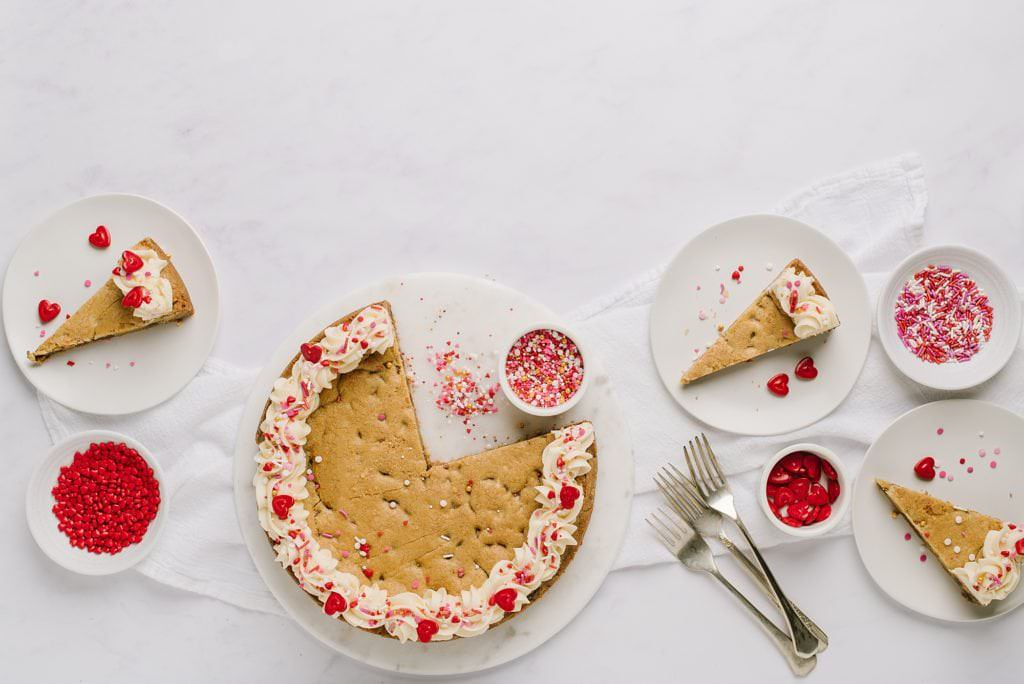 overhead shot of cookie cake with slices and bowls of sprinkles