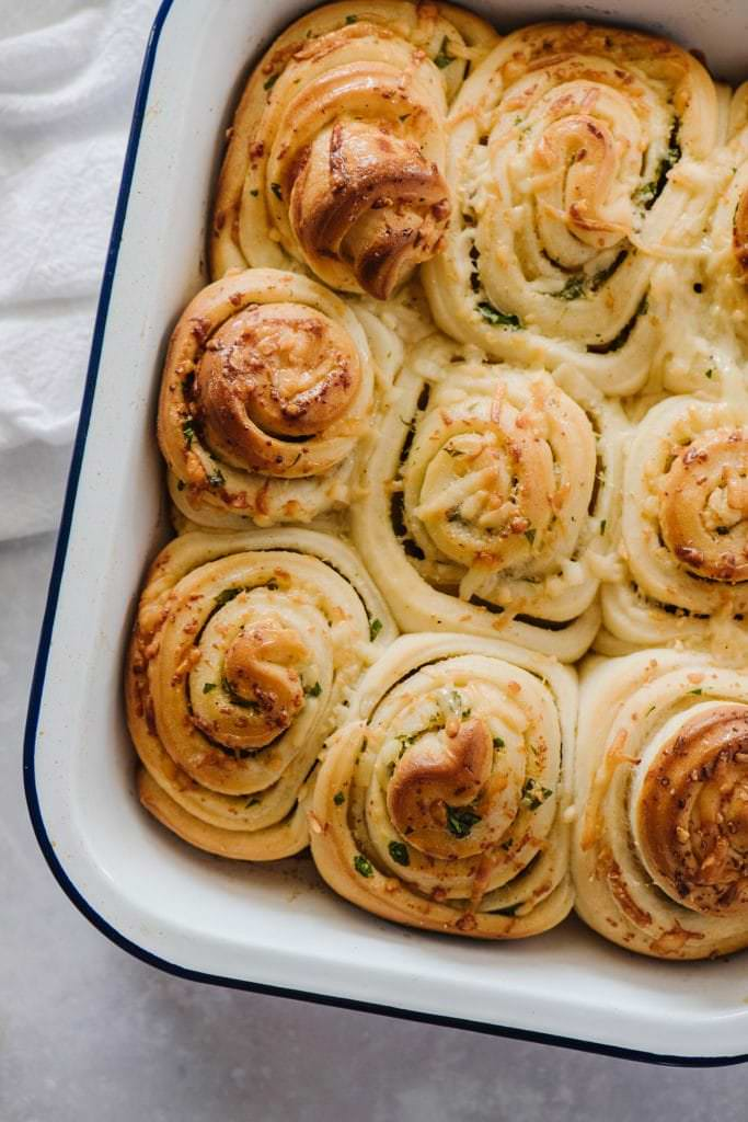 pull apart rolls with garlc butter in white ceramic baking dish with white towel