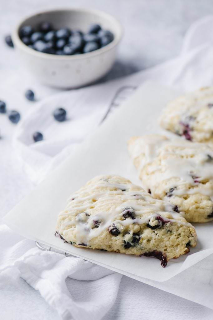 blueberry lemon scones on white plate with fresh blueberries in white bowl
