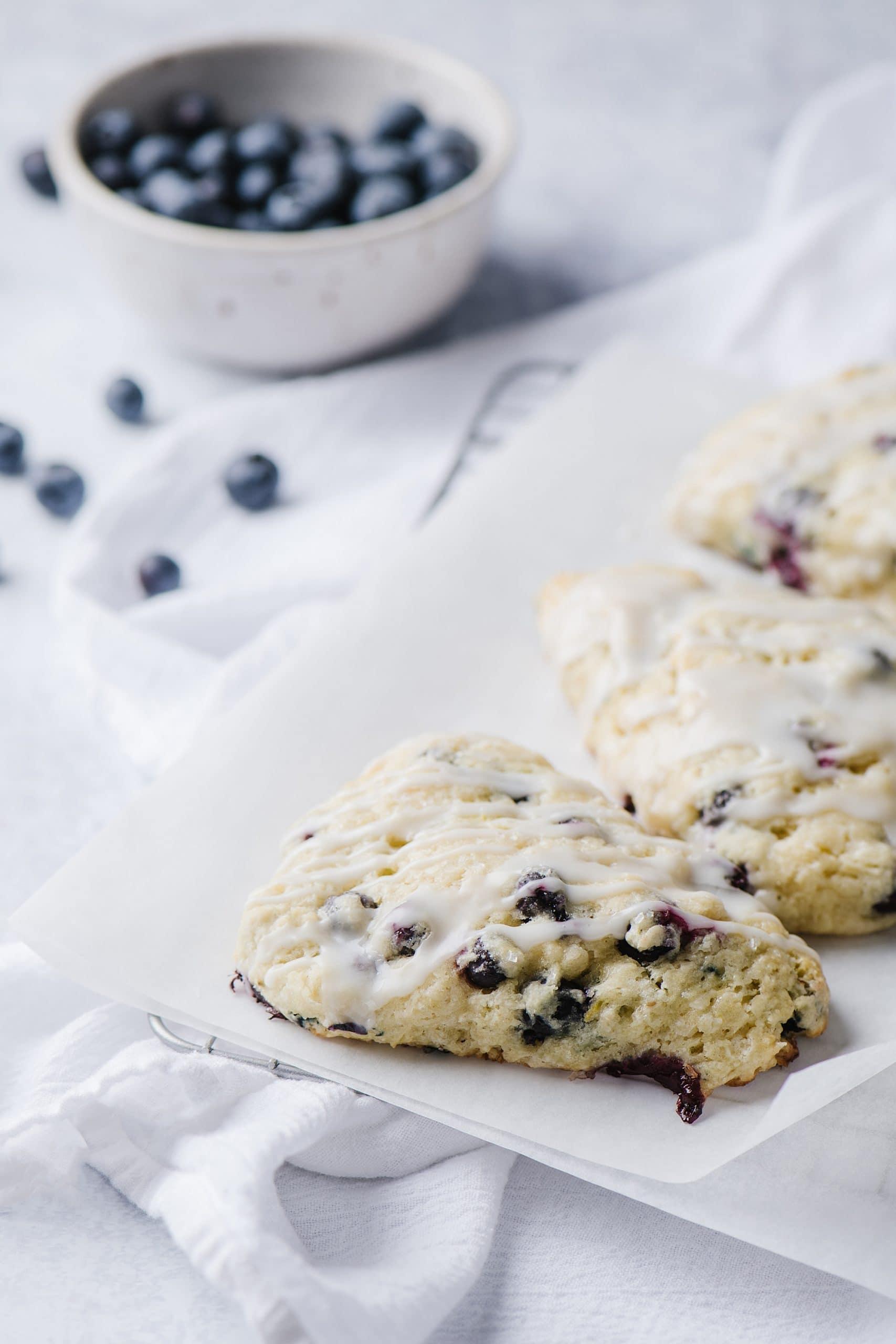 blueberry lemon scones on white plate with fresh blueberries in white bowl