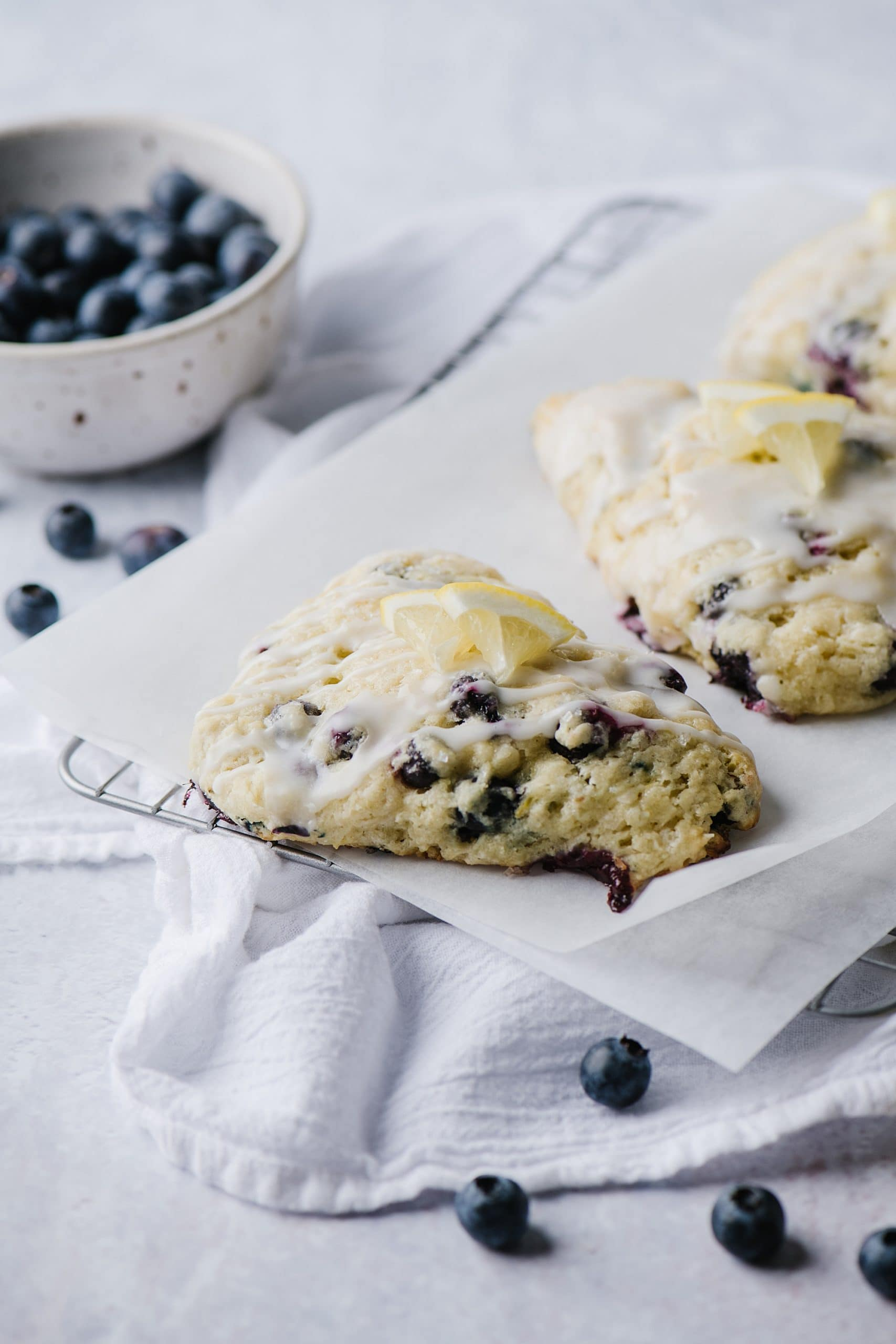scones with blueberries and lemon glaze on parchment paper with blueberries in white bowl