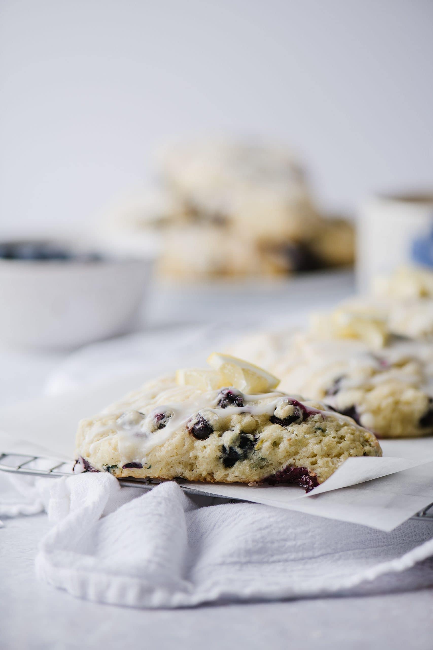 blueberry scones with lemon glaze on parchment paper