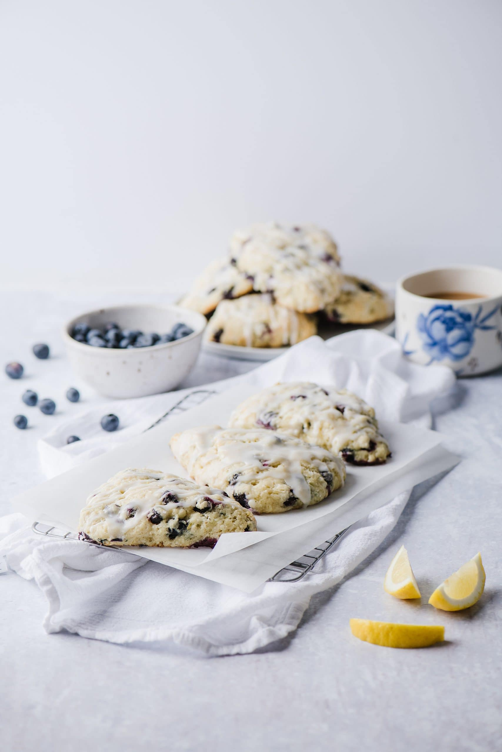 blueberry lemon scones on white plate with fresh blueberries in white bowl and mug of tea