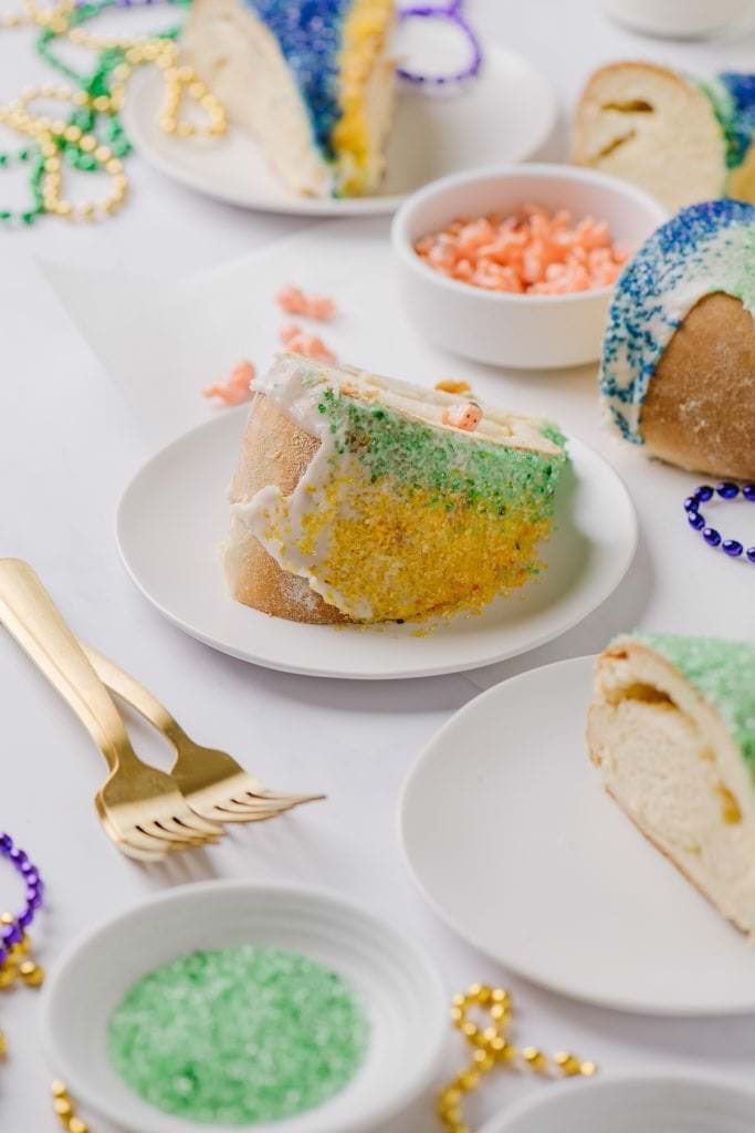 slice of homemade Mardi Gras cake on white plate with plastic babies in white bowl and two gold forks