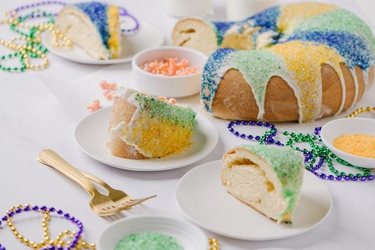 sliced Fat Tuesday cake on white plates with sprinkles