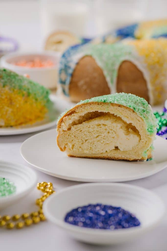 cream cheese filled king cake on white plate with glazed cake in background