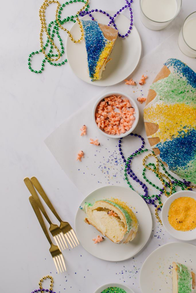 glazed, decorated and sliced Mardi Gras cake on white plate with gold forks and bead necklaces