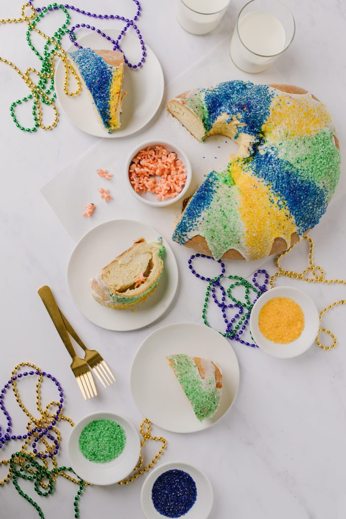 sliced king cake with slices on white plates, sanding sugar in bowls and pastry brush