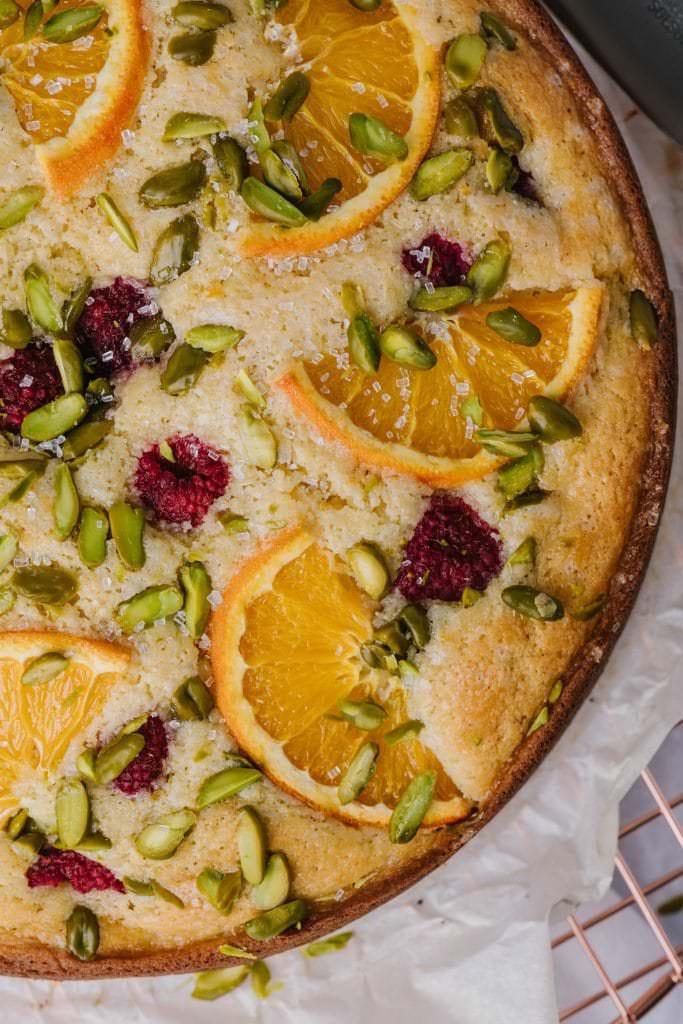 close up shot of raspberry orange pistachio ricotta cake