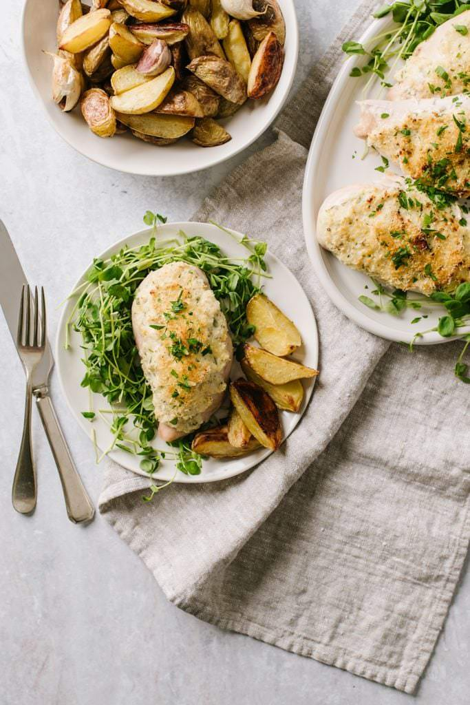 easy chicken dinner in white plate with greens, on white platter with bowl of potatoes