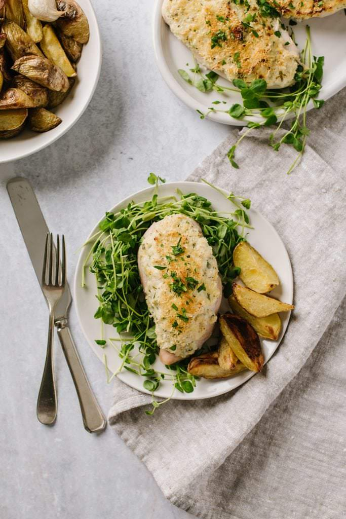 easy weeknight chicken breast with greens and potatoes on white plate with fork and knife