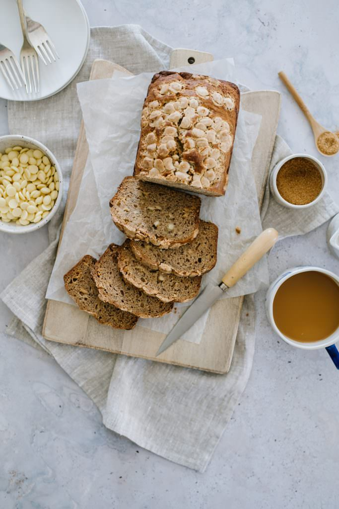 easy banana bread recipe on cutting bowl with bowl of white chocolate chips and coffee