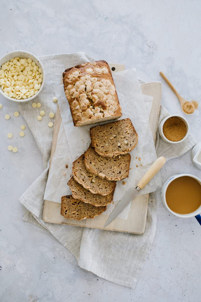 moist banana bread recipe with a bowl of white chocolate chips and a coffee cup
