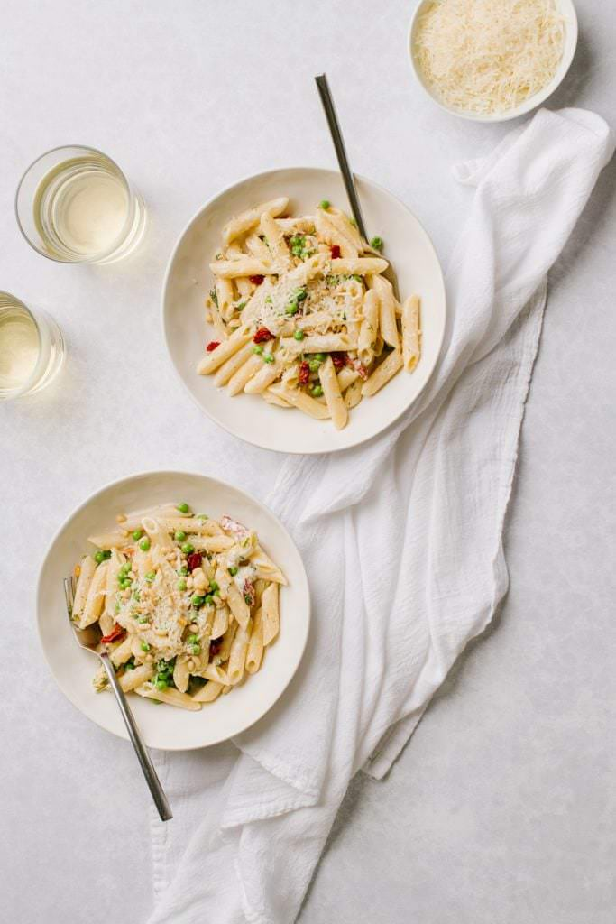 creamy pasta with boursin cheese and green peas in two white bowls with glasses of white wine