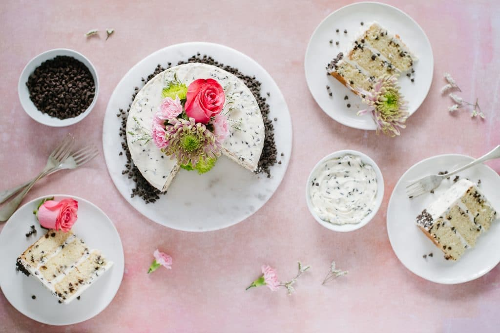 sliced chocolate chip layer cake with buttercream and flowers on cake stand