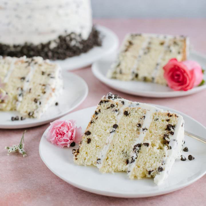 three slices of yellow cake with chocolate chips and buttercream on white plate with cake in background