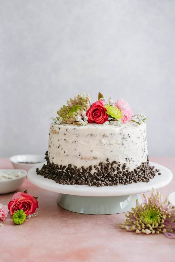 double chocolate chip cake with buttercream and flowers on cake stand