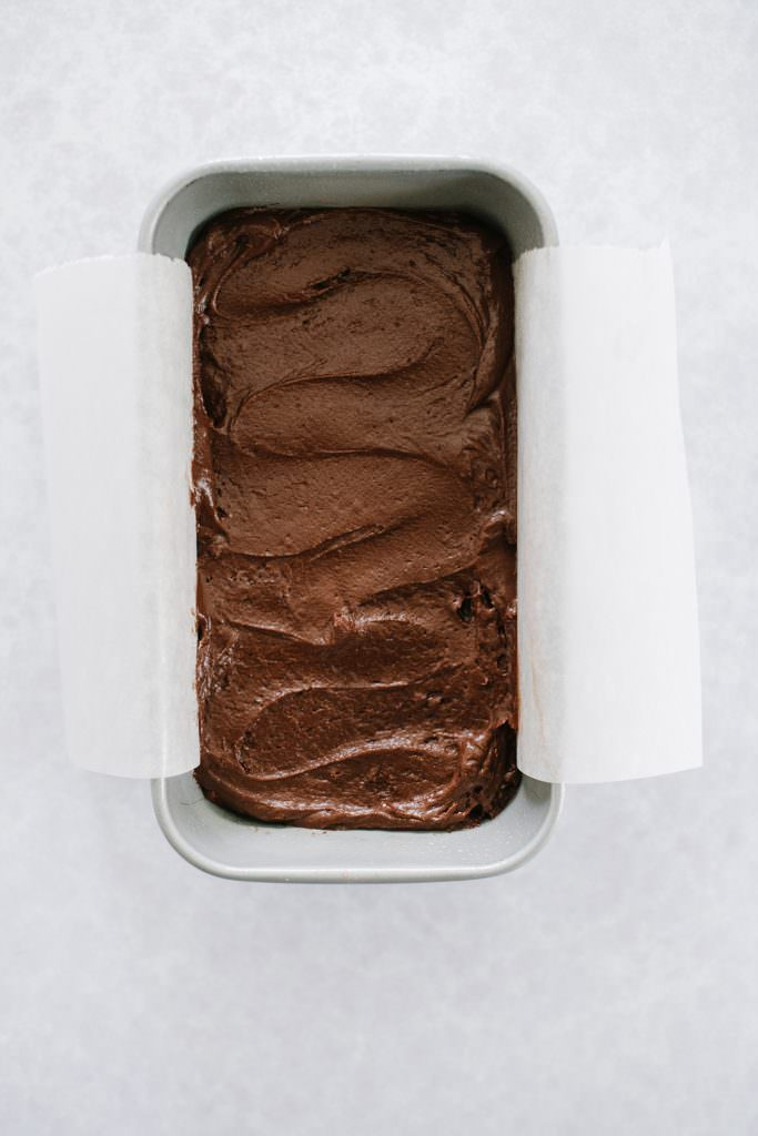 chocolate cake batter in parchment lined loaf pan