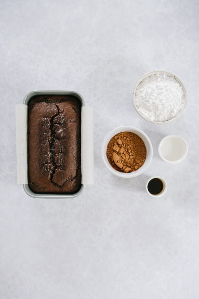 chocolate cake in loaf pan with cocoa powder, powdered sugar, water, vanilla