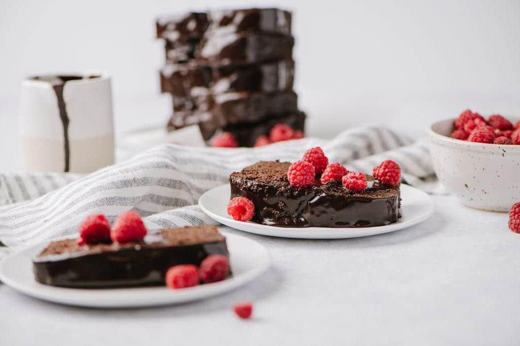 slice of chocolate yogurt cake with chocolate glaze and raspberries on two white plates