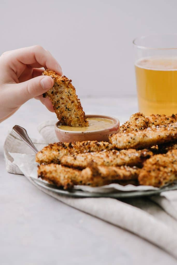 A person dipping an air fryer everything chicken finger into a bowl of honey mustard dip