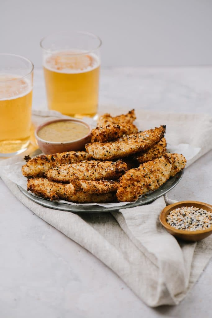 a bowl of everything seasoning next to a plate of air fryer chicken fingers with two beers next to it