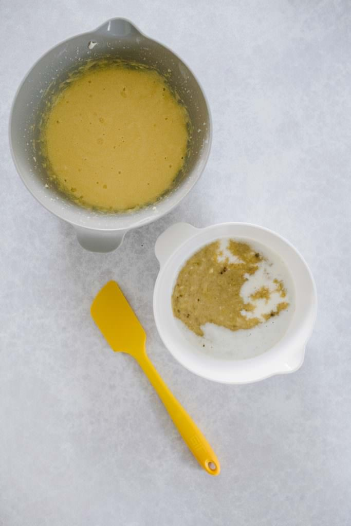 mashed bananas in mixing bowl, dry ingredients in white bowl, yellow spatula