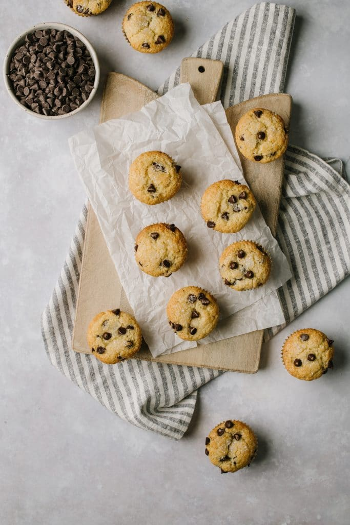 the best chocolate chip muffins on a table with a bowl of chocolate chips