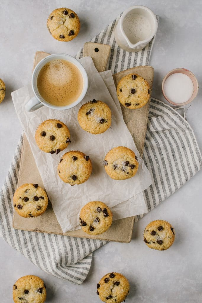 scattered chocolate chip muffins on a table with a cup of coffee creamer and a bowl of sugar
