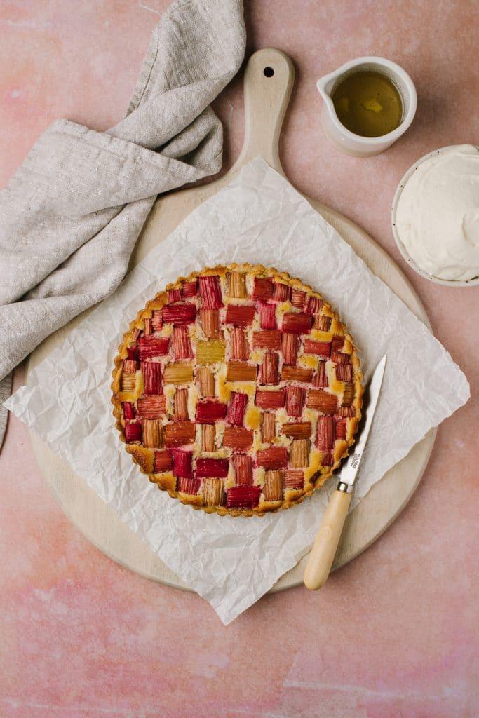 rhubarb frangipane tart on a platter with diplomat cream and vanilla ginger syrup