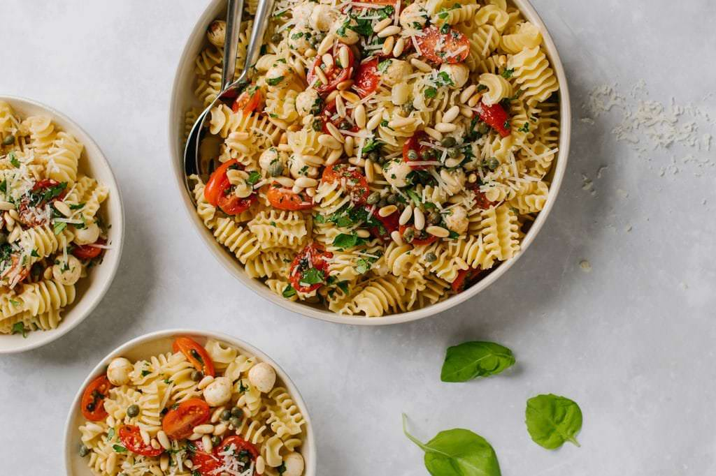 fresh tomato and basil pasta in large white bowl with basil leaves and two small bowls with fresh basil leaves