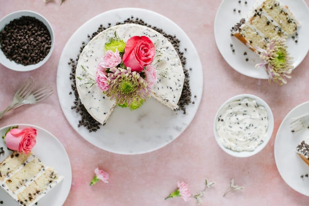 overhead shot of chocolate chip cake with bowl of chocolate chip buttercream and slices of cake on plates