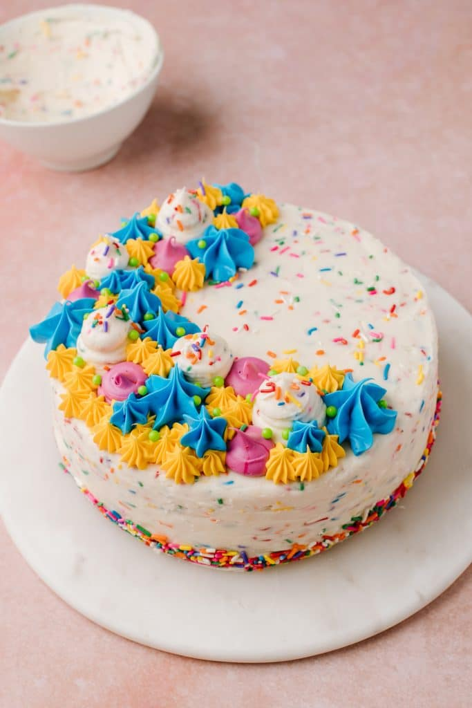 colorful and decorative funfetti cake with sprinkles on white platter