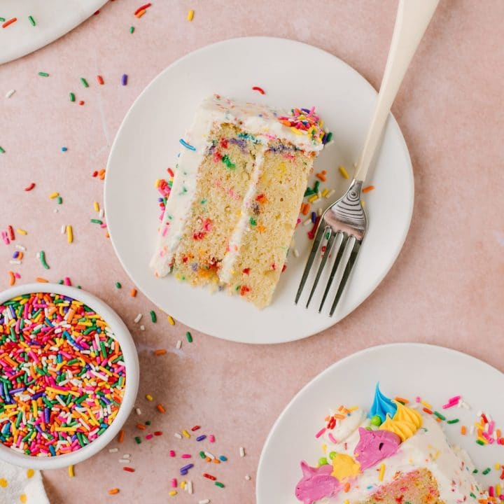 slices of vanilla cake with rainbow sprinkles on white plates with fork and sprinkles on side