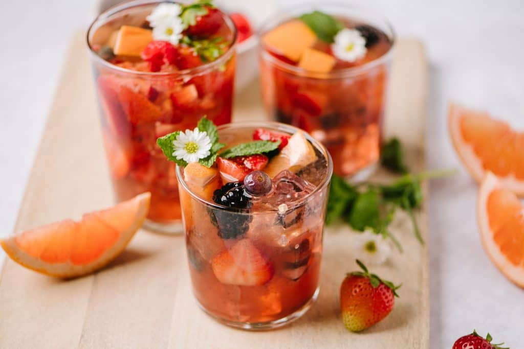 close up shot of three glasses of rose sangria with strawberries blueberries raspberries blackberries and grapefruit
