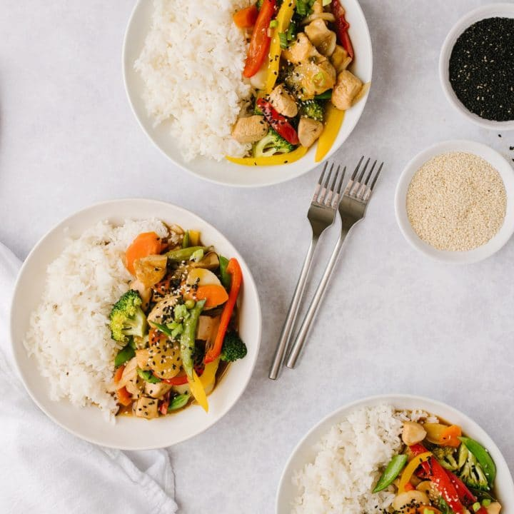 bowls of healthier orange chicken and vegetables with two forks and two bowls of sesame seeds