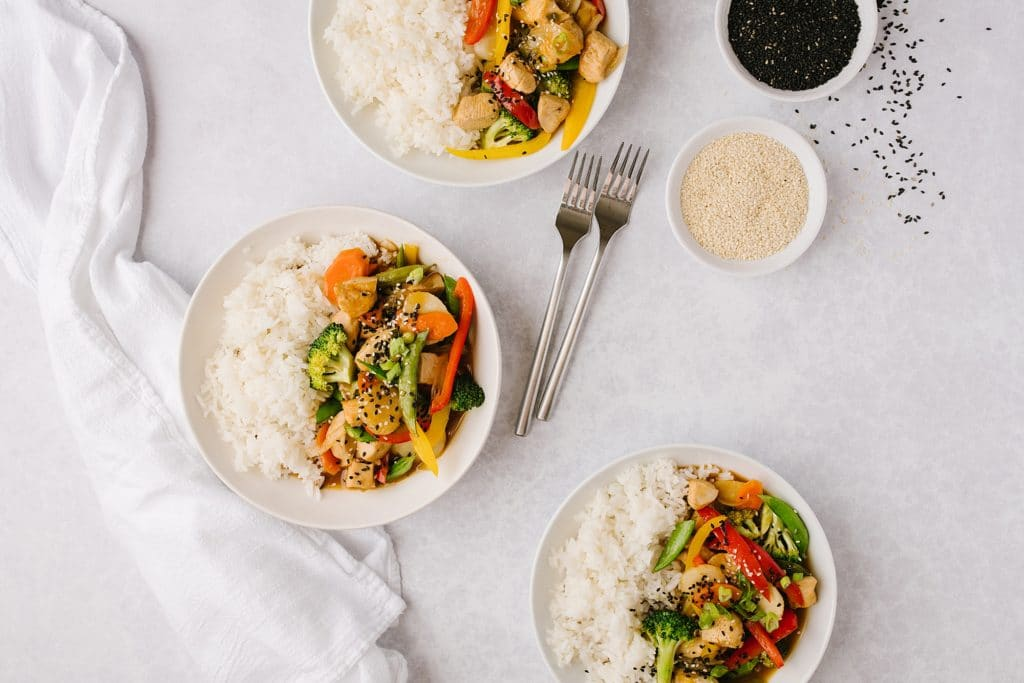 three bowls of healthier chicken and vegetables and rice with two forks and two side bowls of black and white sesame seeds