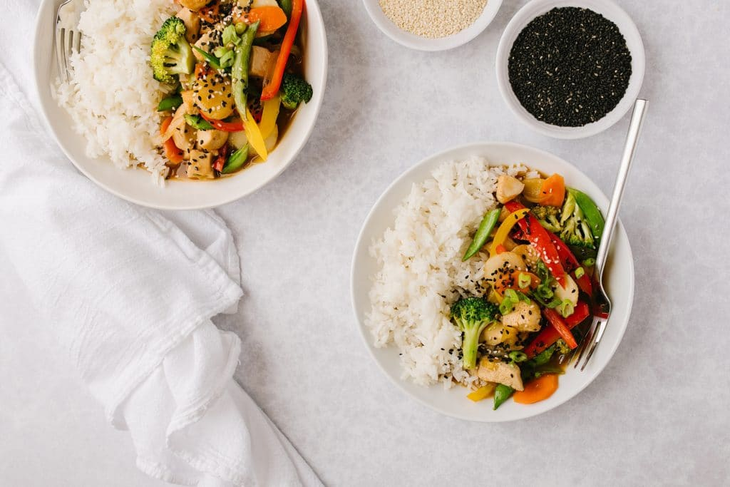 two bowls of healthier chicken and vegetables and rice with two forks and two side bowls of black and white sesame seeds