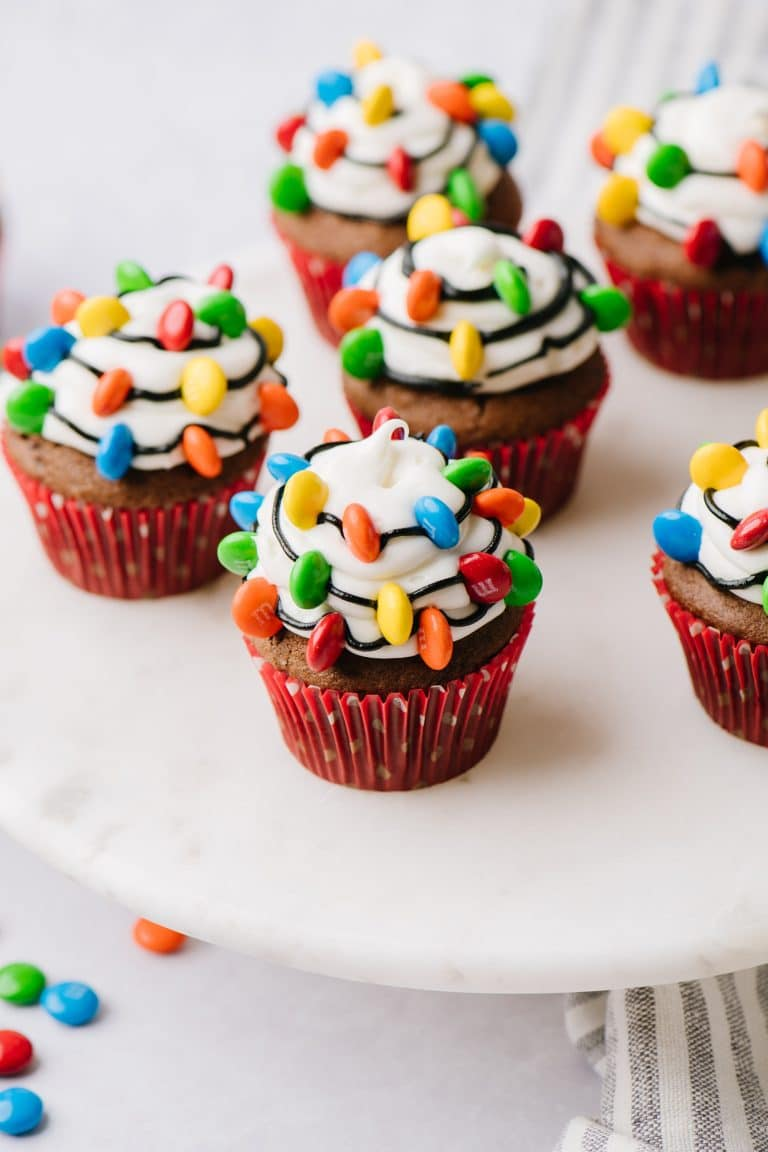 chocolate cupcakes decorated with vanilla frosting, black strings and m&ms