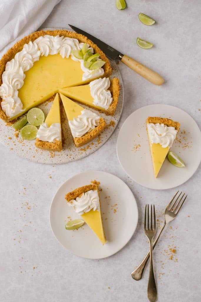 slices of the best key lime pie recipe on white plates with forks and whole pie on the side