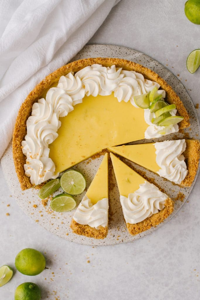 easy key lime pie recipe topped with whipped cream and sliced with fresh limes on the side