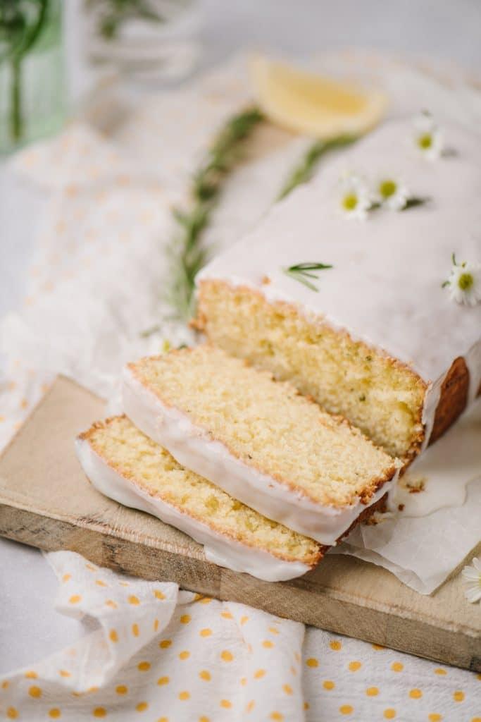 easy lemon rosemary cake with lemon drizzle sliced on wooden board