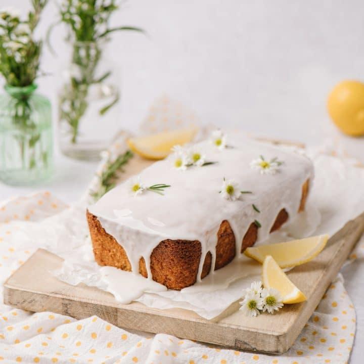 moist lemon cake with lemon glaze on wooden board with fresh lemon slices and rosemary sprigs