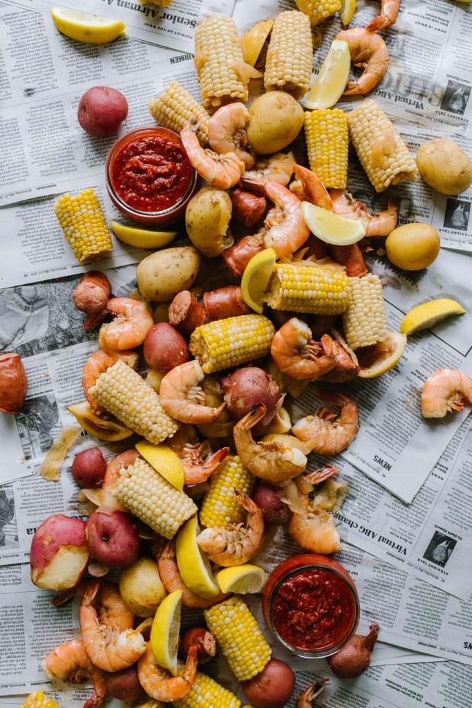 pile of shrimp, sausage, corn, potatoes on newspaper